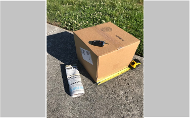 Cardboard box with tape measure, newspaper, and keys